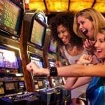 three women cheering in front of a slot machine