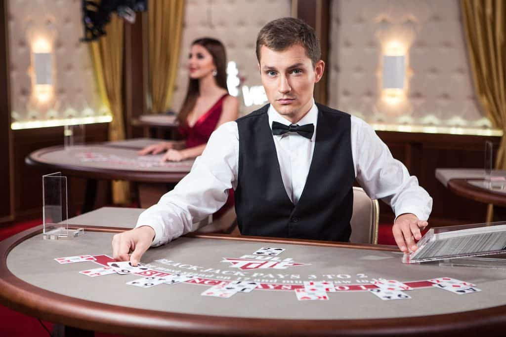 a male casino dealer holding poker cards