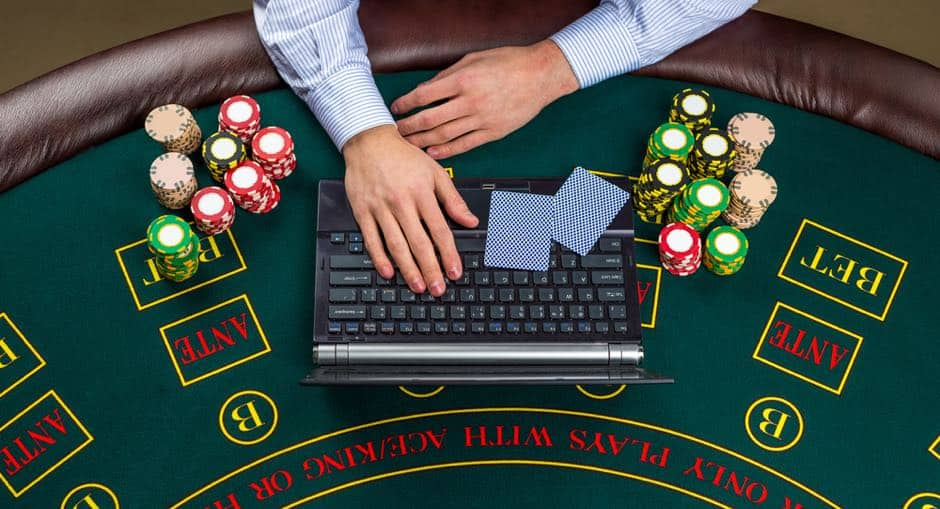 a man with a laptop and poker chips on his side
