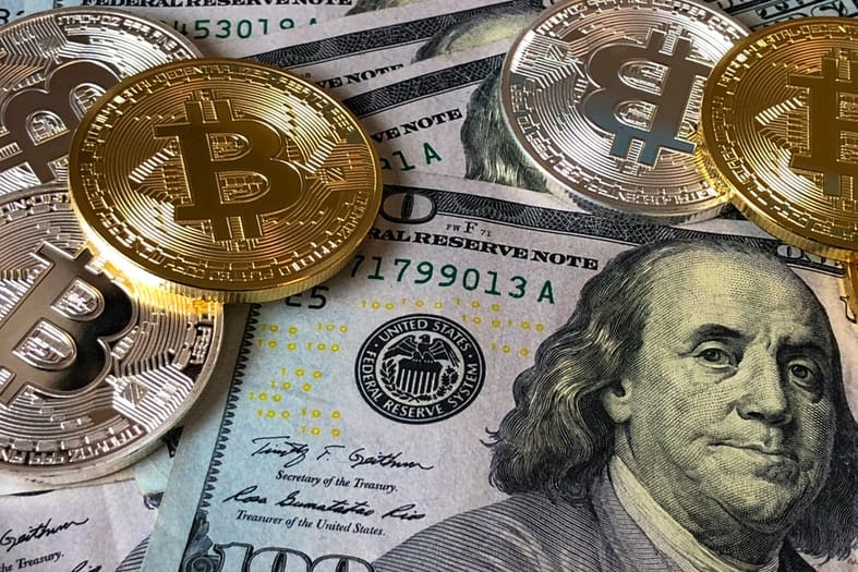 100 dollar bills on a table with gold and silver bitcoin monets on top