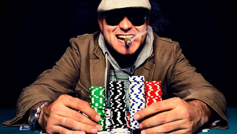a happy man with a cigarette in his mouth holding a big stack of poker chips