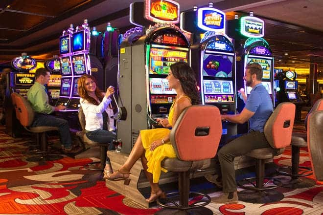 three people sitting and playing the slot machines