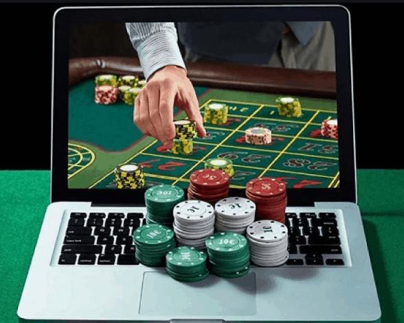 laptop with the screen showing a hand holding poker chips on a poker tablw