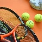 tennis rackets with green balls and a sneaker next to it
