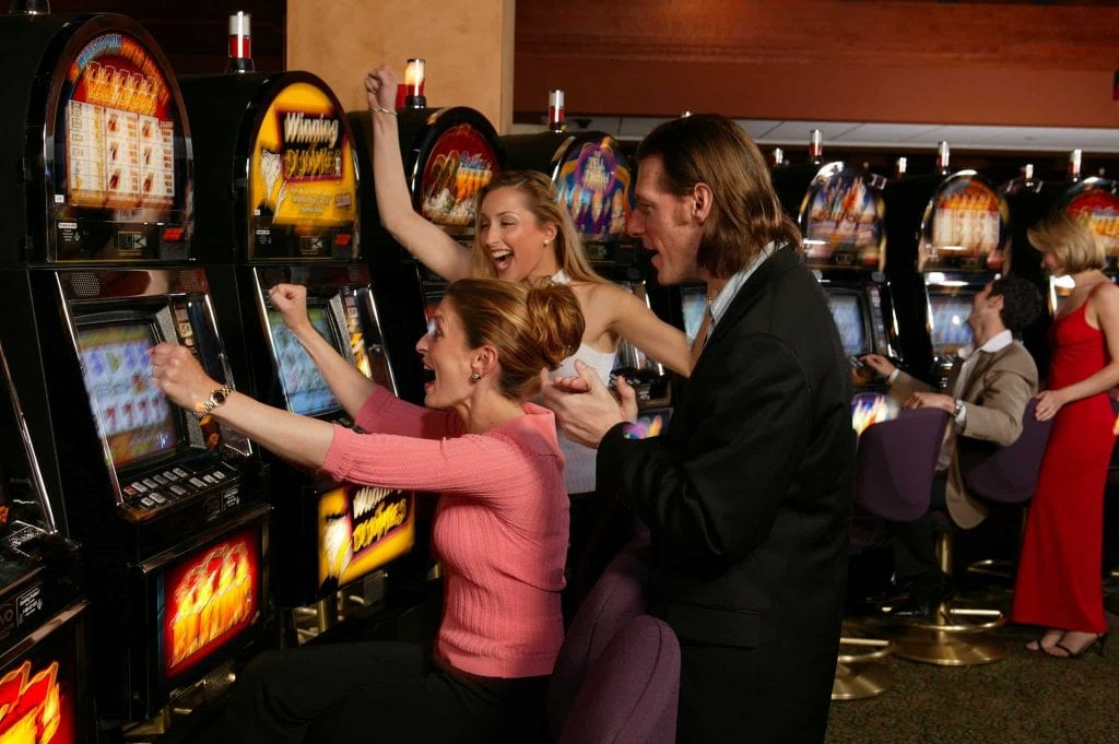 three people cheering in front if a slot machine