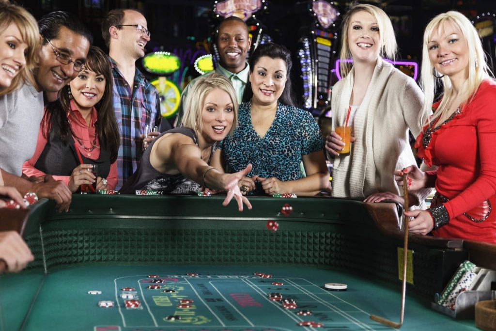 a woman throwing dices on a casino table